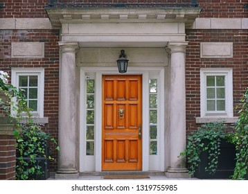 elegant wooden front door and stone columns of portico entrance