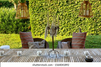 Elegant wooden garden furniture on terrace of suburban home looking out on the green of the garden
