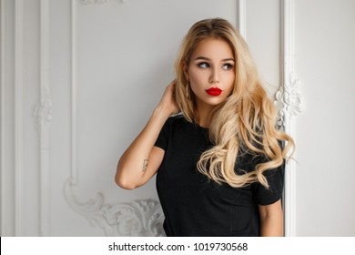 Elegant young beautiful woman with red lips in a black stylish T-shirt near a white vintage wall