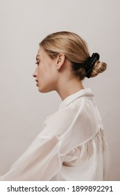 Elegant young blonde in white silk shirt and black hair scrunchie, with trendy hairstyle, turning head aside and looking down against light background