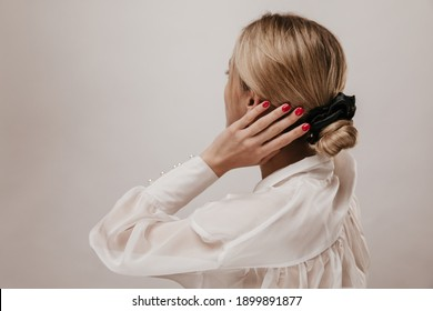 Elegant young blonde-haired lady in white silk blouse and black scrunchie, adjusting trendy hairstyle and posing isolated over light background