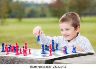 Elegant young boy in white shirt learning to play chess with blue and red chess pieces on wood table in the park