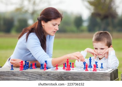 Elegant young boy in white shirt and his mother learning to play chess with blue and red chess pieces on wood table in the park