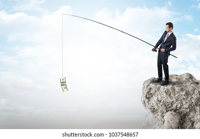 Elegant young businessman fishing cash from a huge rock