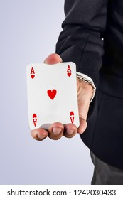 an elegant young businessman holding a ace of hearts in his hand