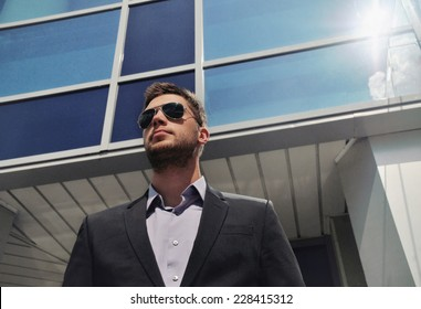 elegant young businessman in suit on the skyscraper background, business concept