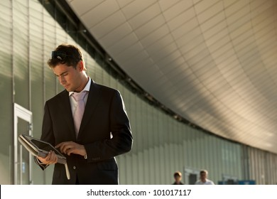 Elegant young businessman using his PC tablet while walking
