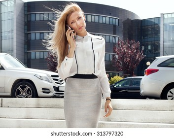 Elegant young businesswoman working, talking by mobile phone. Outdoor photo. Sunny day.