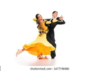 elegant young couple of ballroom dancers dancing on white