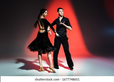elegant young couple of ballroom dancers dancing in red light