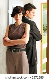 elegant, young couple standing back to back in a room