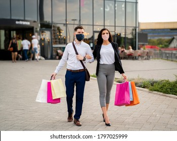 Elegant young couple wearing masks over face , going home after shopping in modern mall, coronavirus and clothes shopping
