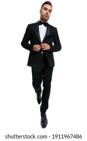 elegant young fashion man buttoning black tuxedo and walking isolated on white background in studio, full body picture