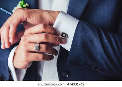 elegant young fashion man fixing cufflinks