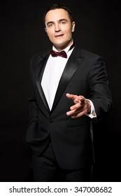 Elegant young fashion man in tuxedo on black background