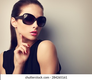 Elegant young female model in trendy sunglasses posing touching hand the face. Vintage closeup portrait with empty copy space