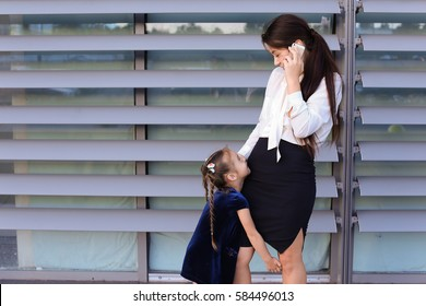 Elegant young female woman, young modern mom, business woman holding mobile phone hand and talking on cellphone, solves problems, negotiates business meeting with partners, spends time girl daughter