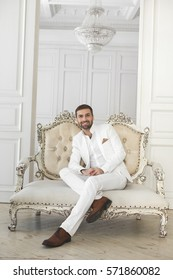 Elegant young handsome man with a beard in a white classic suit. The hotel's interior. Photo Studio. Sofa. Window. Chair. Chandelier