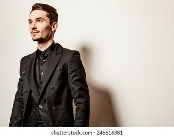 Elegant young handsome man in black costume. Studio fashion portrait.