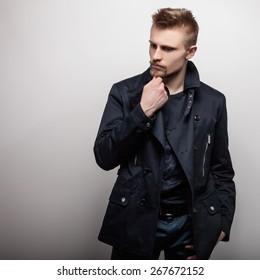 Elegant young handsome man in black coat. Studio fashion portrait.