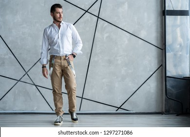 Elegant young handsome man. Good looking young man standing against grey background