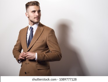 Elegant young handsome man in long stylish coat.