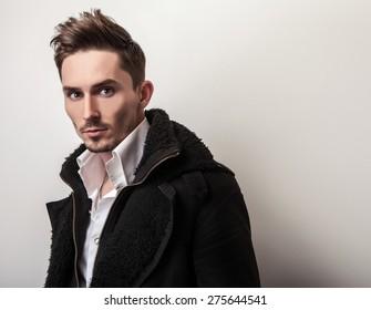 Elegant young handsome man in long stylish black coat. Studio fashion portrait.