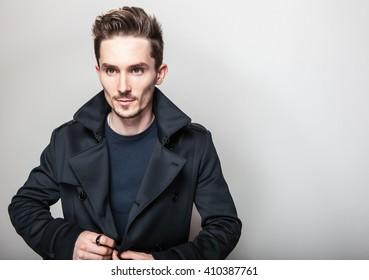 Elegant young handsome man in long stylish dark blue coat. Studio fashion portrait.
