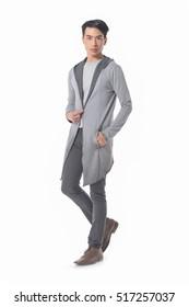 Elegant young handsome man in long stylish coat. Walking in studio