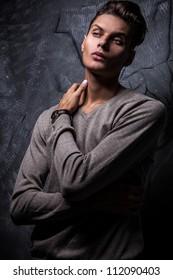 Elegant young handsome man on grunge background. Studio fashion portrait.