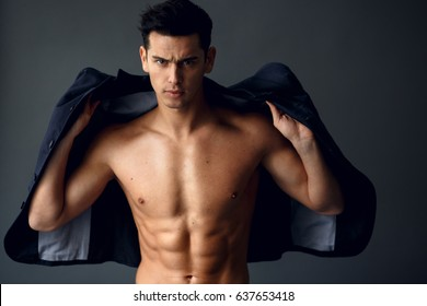 Elegant young handsome man standing and posing in fashionable suit on a naked torso, isolated on grey background. Studio fashion portrait. Vertical view.