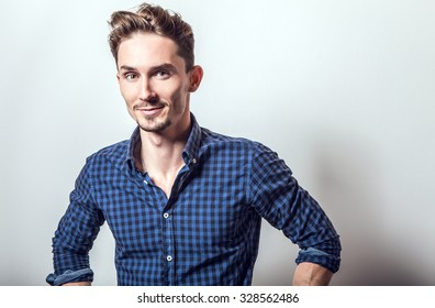 Elegant young handsome man in stylish dark blue shirt. Studio fashion portrait.
