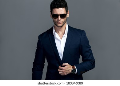 Elegant young handsome man wearing glasses and wathers. Studio fashion portrait.