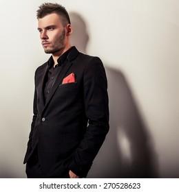 Elegant young handsome serious man in black costume. Studio fashion portrait.