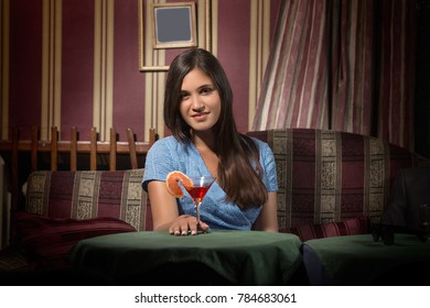 Elegant young lady is drinking cocktail at her luxurious home