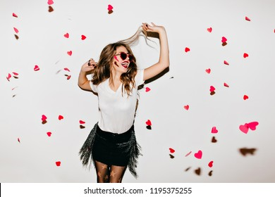Elegant young lady in trendy sunglasses looking up at fallen hearts. Portrait of positive long-haired woman in short skirt enjoying photoshoot.