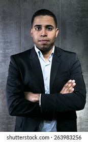 elegant young latin man wearing a suit with arms crossed in front of a gray wall / hispanic businessman