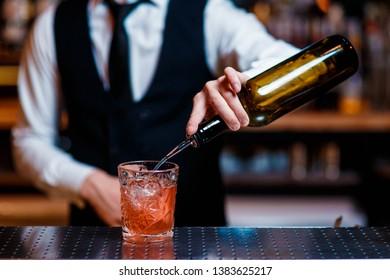 elegant young male barman prepares a delicious cocktail