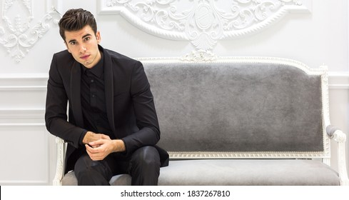 Elegant young male model wearing a suit sitting in a beautiful classy workplace.