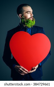 Elegant young man with a beard of green flowers holding red heart. Love concept. Valentine's Day. Barbershop.