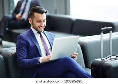 Elegant young man with laptop looking at its display with smile while networking in lounge