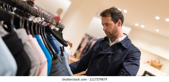 Elegant young man portrait while choosing and trying clothes in a store.