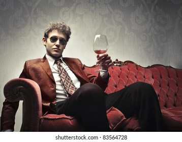 Elegant young man sitting on a velvet sofa and holding a glass of wine