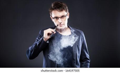 Elegant young man smoking electronic cigarette