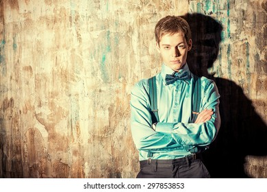 Elegant young man stands by the grunge wall and looking to camera. Men's beauty, fashion. Business.