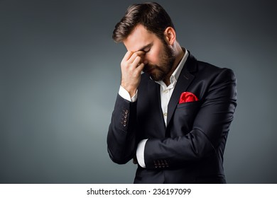 Elegant young man in a suit holding head. Problems, head pain, issues.
