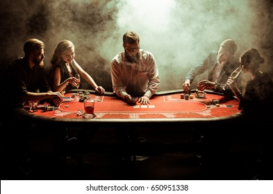 Elegant young men and women playing poker at table in smoke