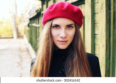 Elegant young Parisian woman outdoors. Beautiful charming girl in red beret. French Style
