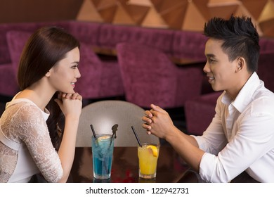 Elegant young people dating in a restaurant enjoying cocktails