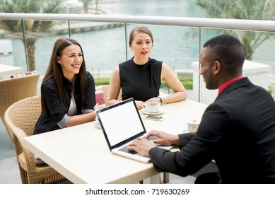 Elegant young people have business meeting at a restaurant near the river.